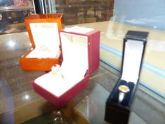 TWO GOLD STONE SET RINGS AND A SILVER RING.