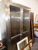 A LARGE BRUSHED STEEL DISPLAY CABINET.
