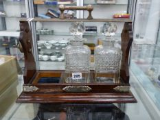 A LOCKING TANTALUS WITH KEY AND TWO CUT GLASS DECANTERS.