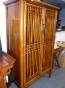 AN ORIENTAL ELM CABINET WITH LATTICE DOORS.