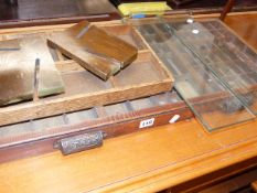 A PRINTER'S TRAY AND A GLASS BOOK TROUGH TOGETHER WITH A WALNUT OCCASIONAL TABLE.