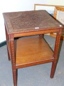 AN ARTS AND CRAFTS MAHOGANY TWO TIER TABLE, THE TOP CARVED IN LOW RELIEF WITH FLOWERS WITHIN CHEVRON