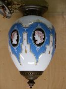 A PRINTED MILK GLASS OVOID LIGHT SHADE WITH BRASS FITTINGS, PUCE CLASSICAL HEADS ON BLACK OVALS