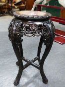 A CHINESE HARD WOOD STAND INLAID WITH MARBLE ROUNDEL ABOVE A PIERCED FLORAL APRON AND CABRIOLE