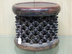 A BAMILEKE SPIDER STOOL, THE DISHED CIRCULAR SEAT LEATHER COVERED. Dia. 35cms