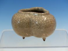 A GUAN TYPE CRACKLED GREY GLAZED TRILOBED BOWL ON THREE BROWN PEG FEET. W 9cms.