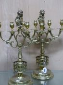 A PAIR OF BRASS FOUR LIGHT CANDELBRA, THE NOZZLES CENTRED BY A LION HOLDING THE ARMORIAL SHIELD OF