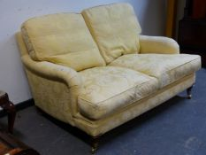 A BESPOKE QUALITY HOWARD STYLE DEEP SEATED TWO SEAT SETTEE WITH FEATHER CUSHIONS IN YELLOW DAMASK