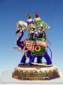 TWO INDIAN ENAMEL ELEPHANTS BEARING JEWELLED HOWDAHS AND WALKING ON STYLISED LOTUS FLOWER BASES. H