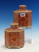 A PAIR OF CHINESE TEA CADDIES AND COVERS, THE HEXAGONAL SECTIONED BODIES PAINTED IN IRON RED WITH