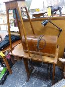 A TREADLE SEWING MACHINE AND A PLANTSTAND.