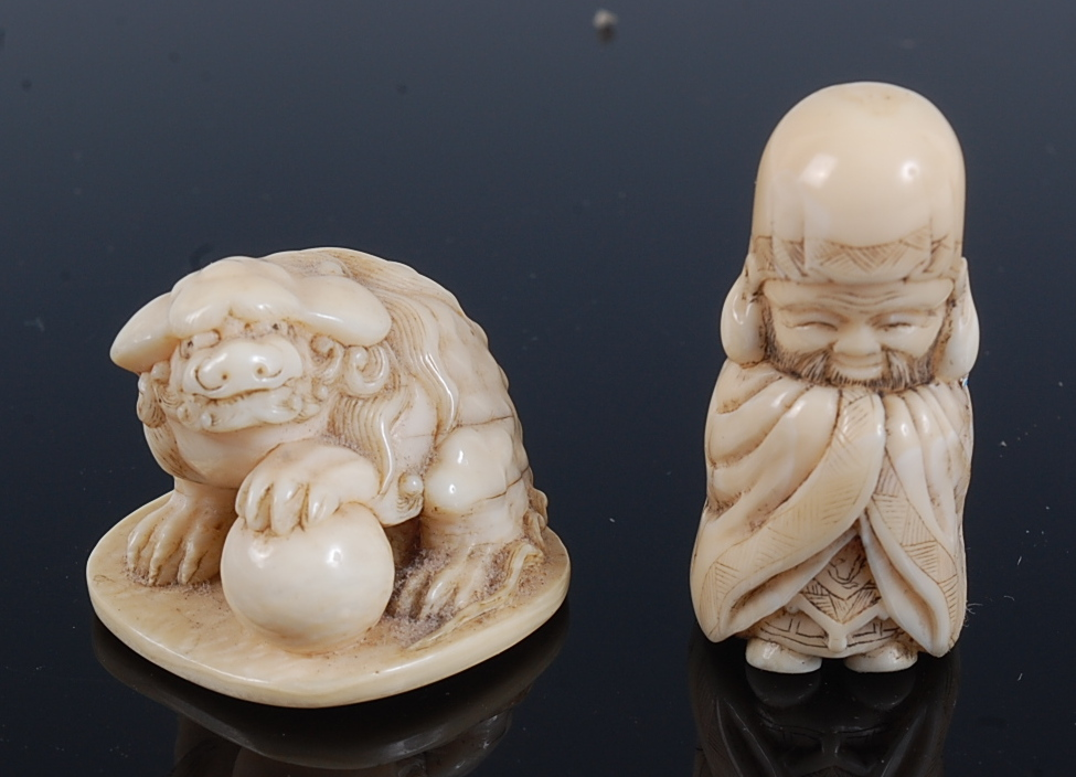 Lot 1322 - A Japanese Meiji period carved ivory netsuke of a shi-shi dog, its left foot upon a ball, signed