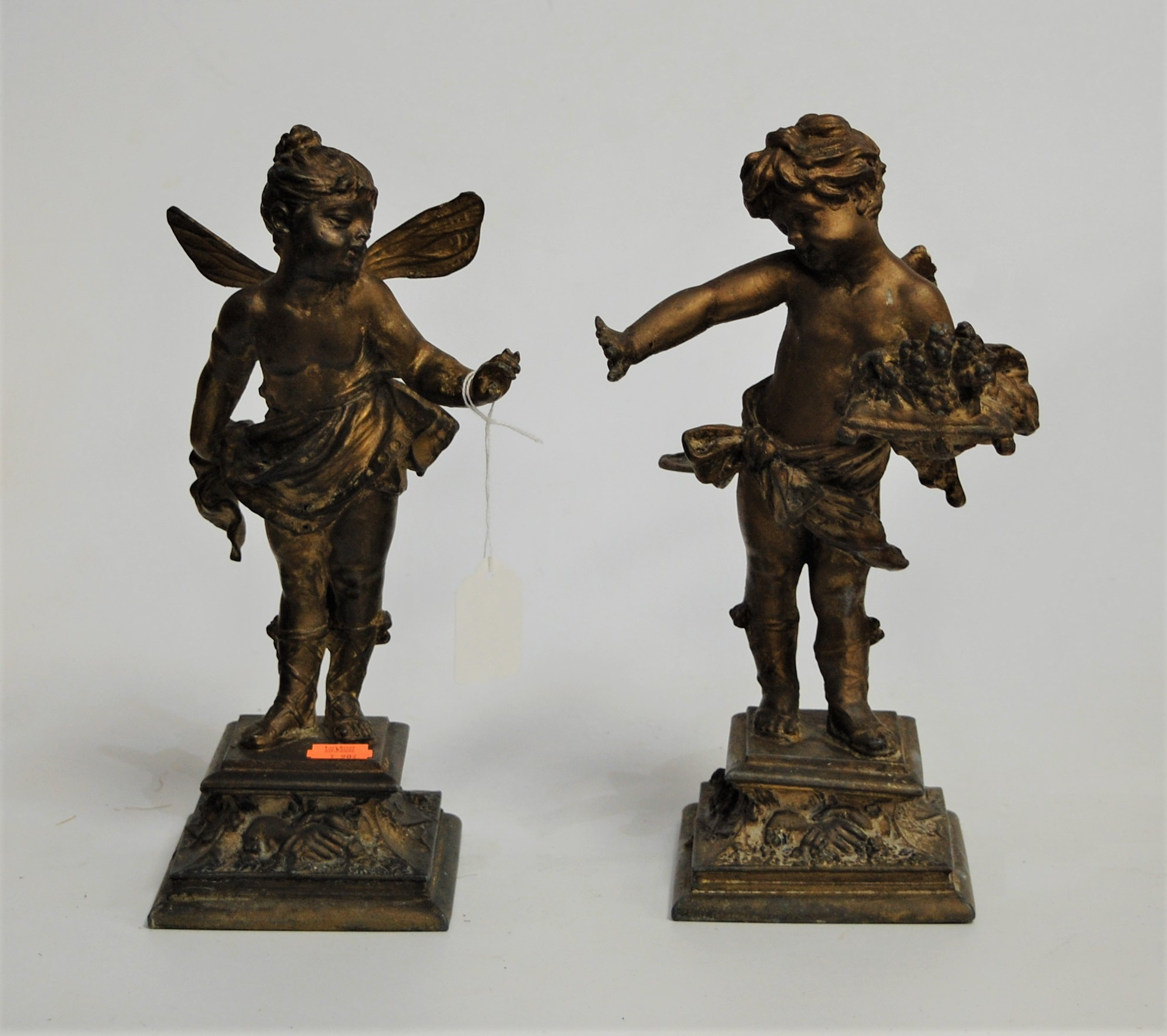Lot 34 - An early 20th century spelter figure of a putti in standing pose, on a concave square plinth;