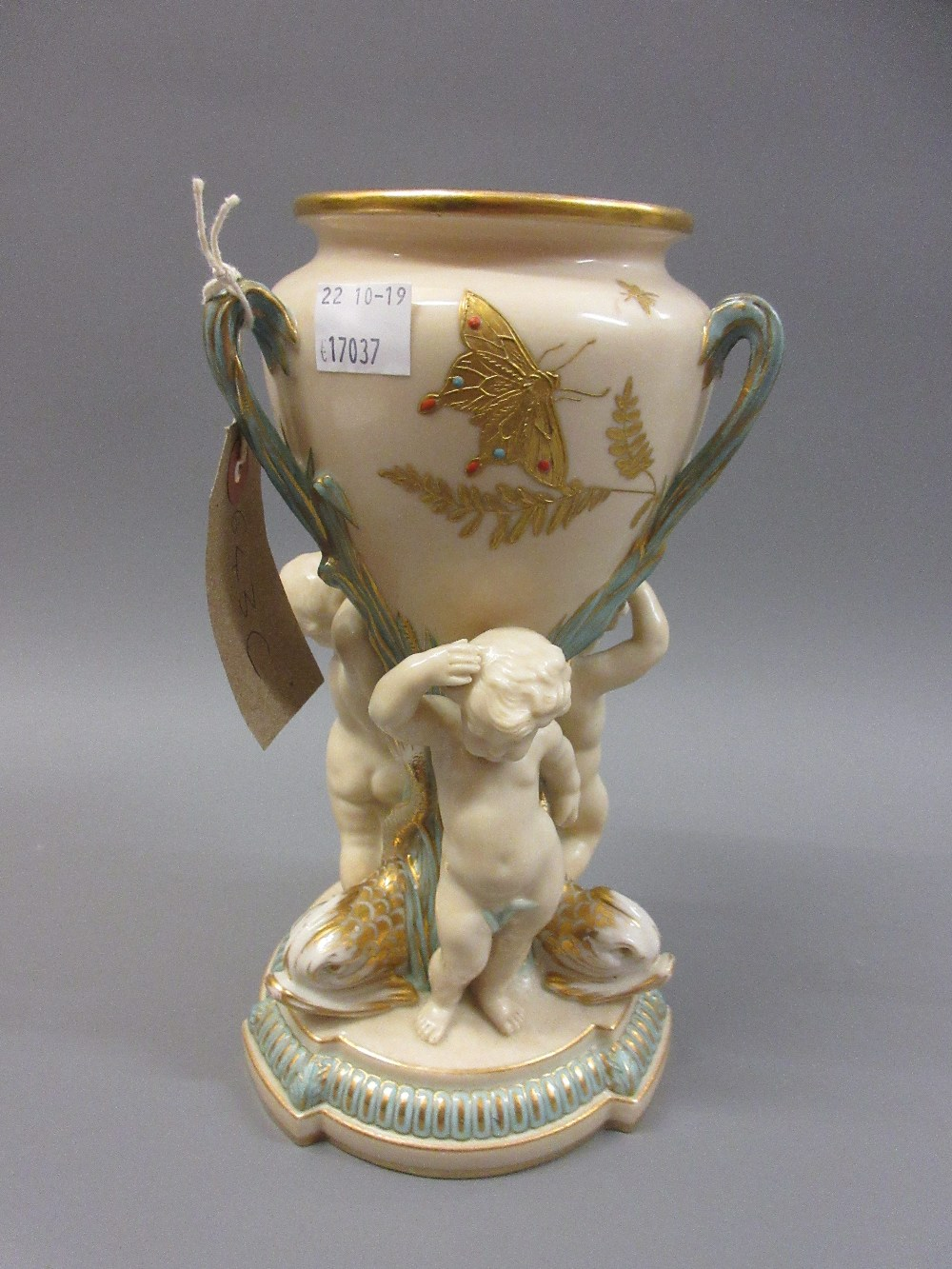 Lot 643C - 19th Century Copeland vase supported by three puti, 9ins high Chip to foot and restoration to two of