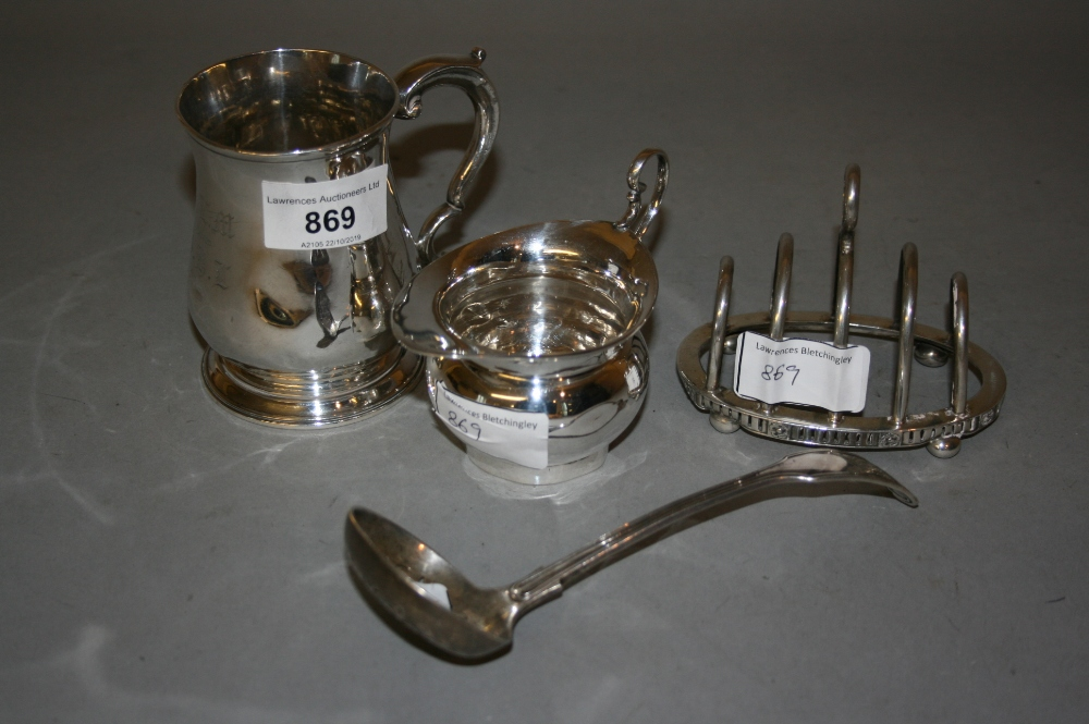 Lot 869 - Small George III silver baluster form mug, silver jug, four division silver toast rack and a