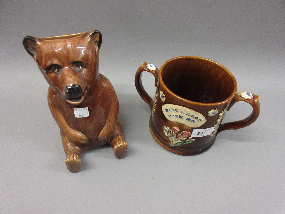 Lot 847 - 19th Century Staffordshire treacle glazed two handled loving cup ' Have a Drop with Me ', together