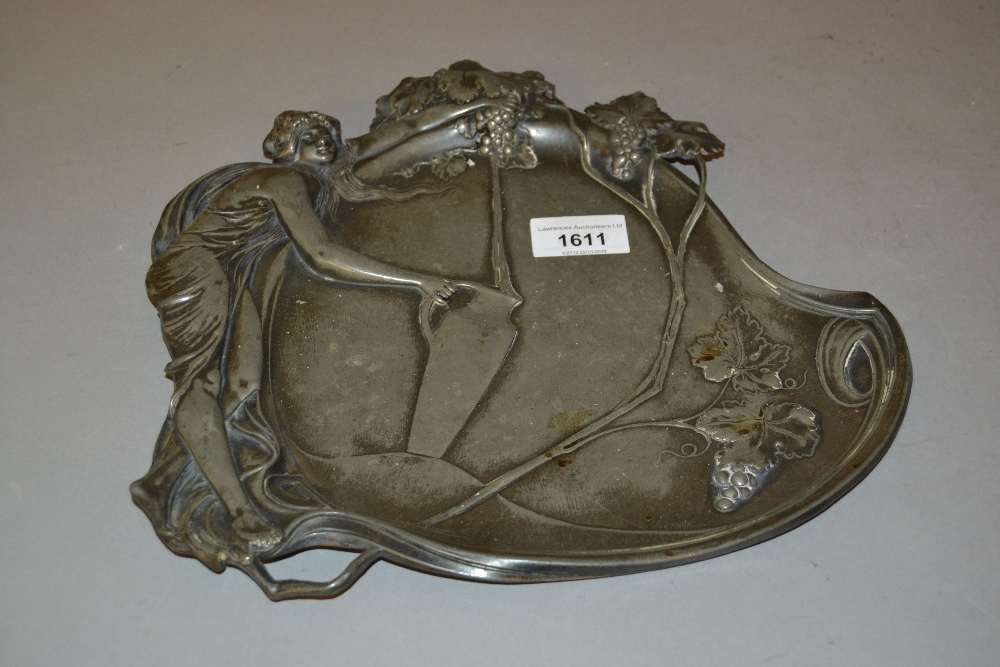 Lot 1611 - Art Nouveau pewter dish decorated with a classical maiden holding a jug above grapes, No. 252 to the