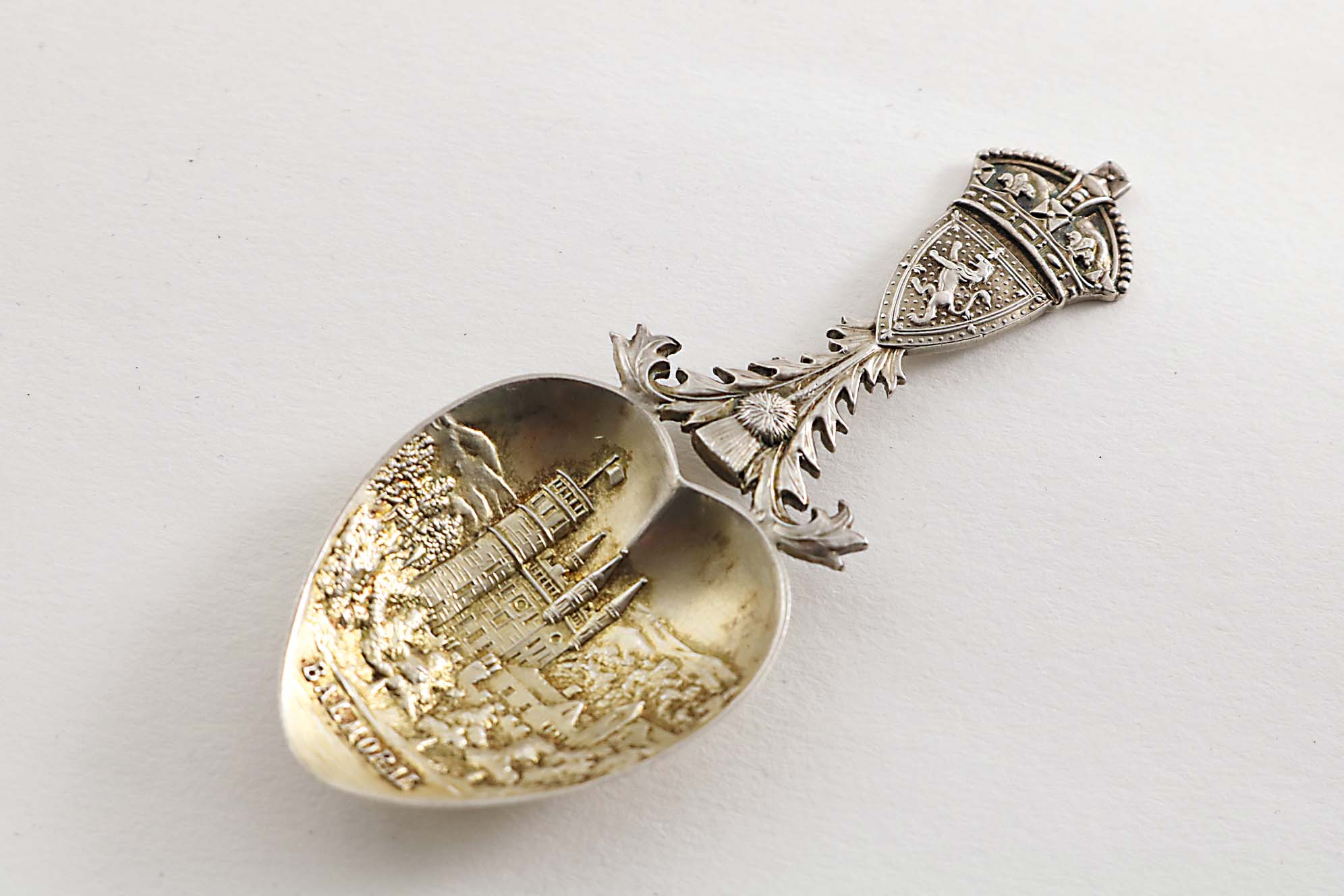 Lot 617 - AN EDWARDIAN PARCELGILT CAST CADDY SPOON with the Arms of Scotland, The Royal Crown and a Thistle on