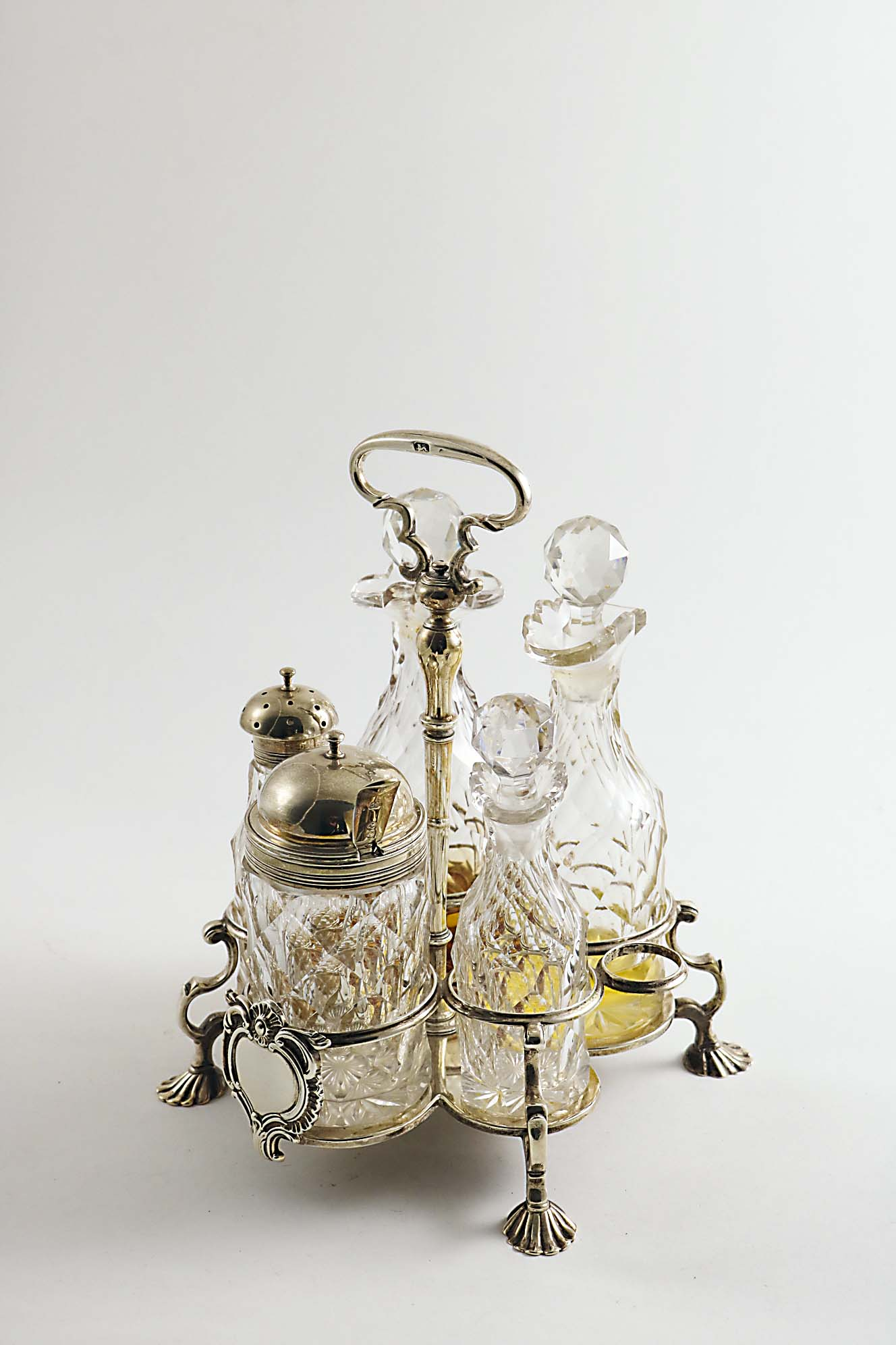 Lot 413 - A GEORGE II WARWICK CRUET FRAME by Samuel Wood, London 1736, fitted with five later faceted cut-