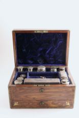 Lot 539 - A VICTORIAN BRASS BOUND ROSEWOOD DRESSING CASE fitted with various mounted cut-glass bottles/jars, a