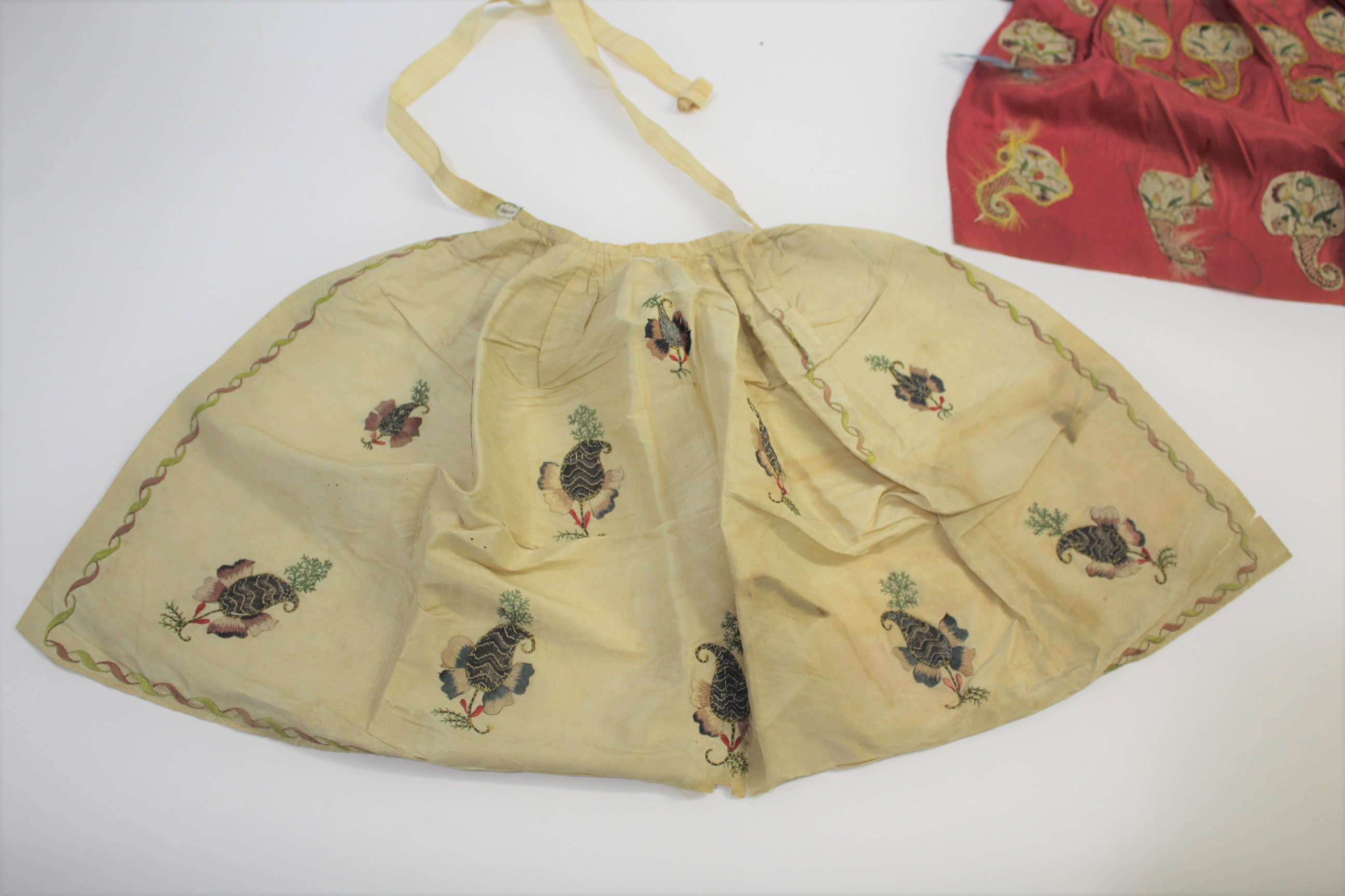 Lot 1855A - 19THC SILK EMBROIDERED APRON a small cream silk apron embroidered with stylised flowers worked in