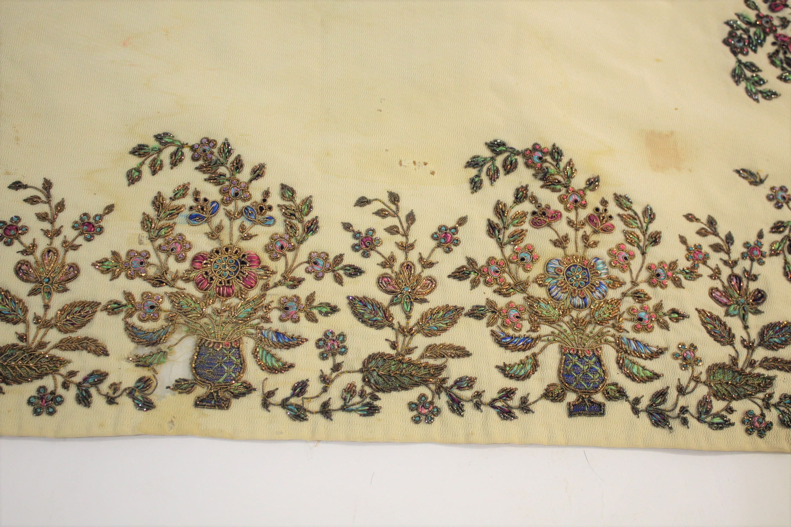 Lot 1896 - ANTIQUE EMBROIDERED SILK PANEL possibly Indian, a cream silk panel with jewel coloured silks and
