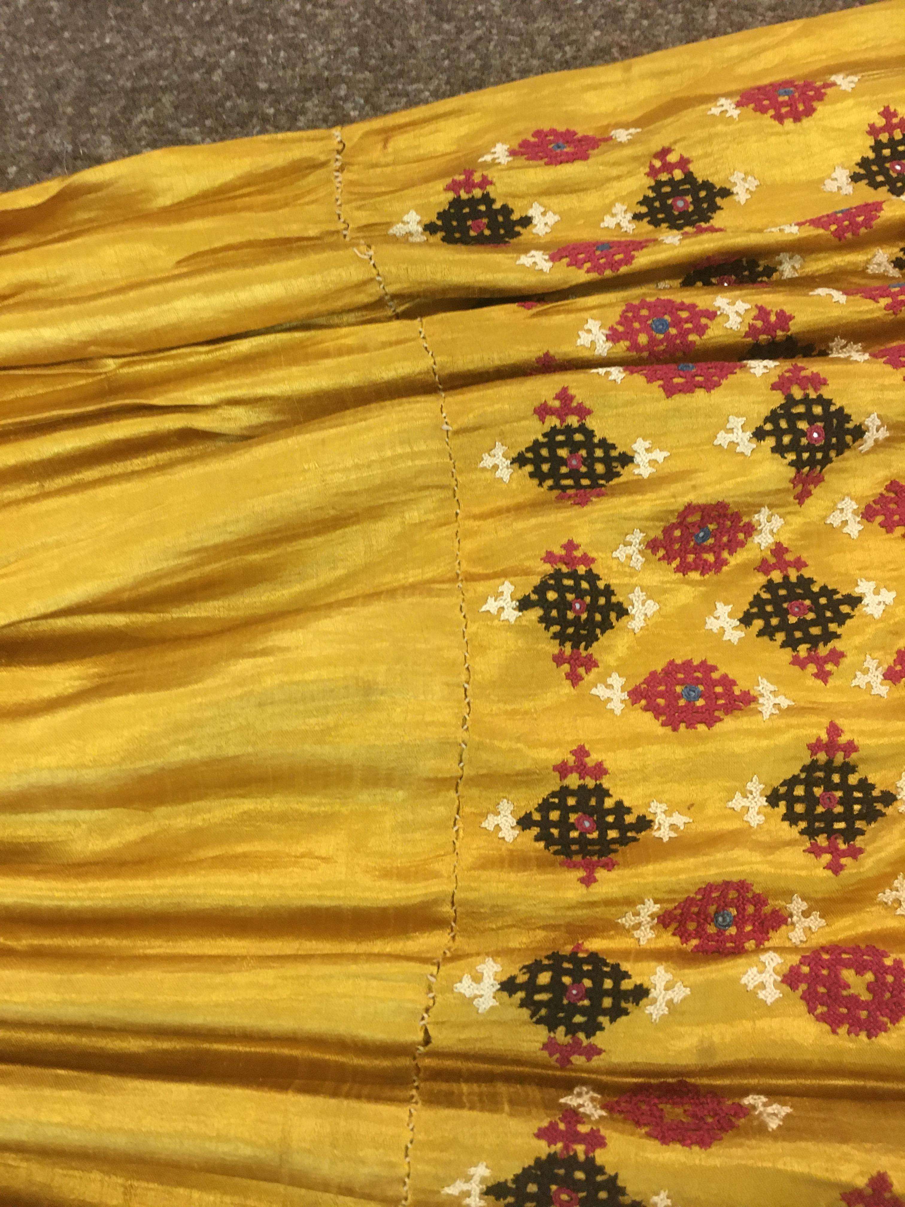 Lot 1890 - ANTIQUE INDIAN SKIRT a full length gathered skirt made from 19thc gold coloured silk, embroidered