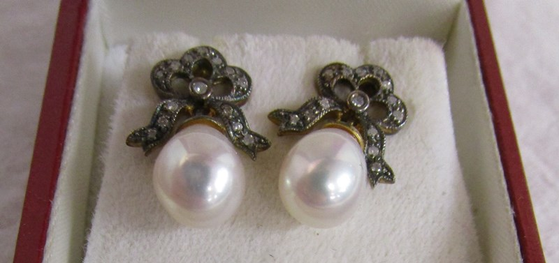 Lot 14 - Pair of bow topped diamond & pearl earrings