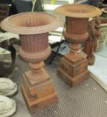 Lot 42 - FLUTED URNS ON PEDESTALS, a pair, in rustic cast iron finish, 101cm H.