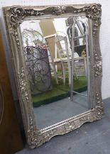 Lot 65 - MIRROR, bevelled in an ornate silver painted frame, 110cm x 79cm.