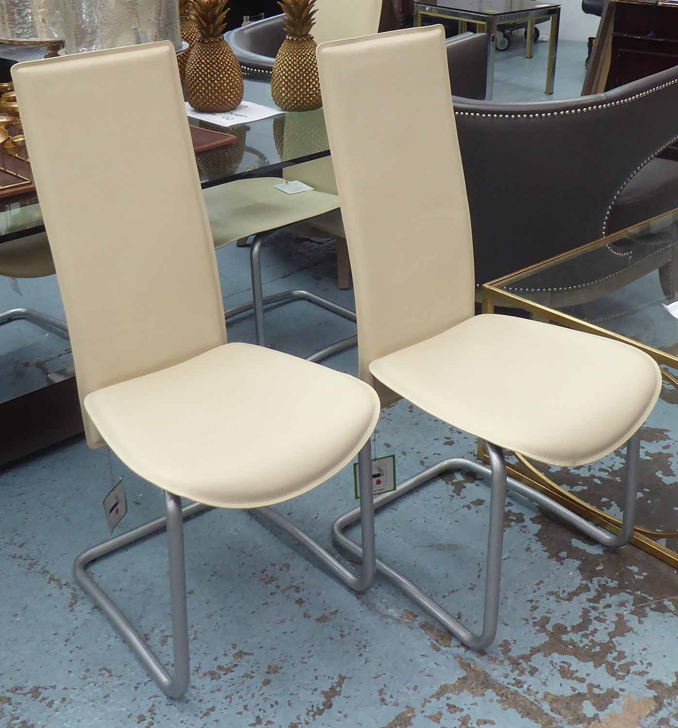 Lot 45 - DINING CHAIRS, by Liquid Concept, a set of six, cream stitched leather on tubular metal frames.