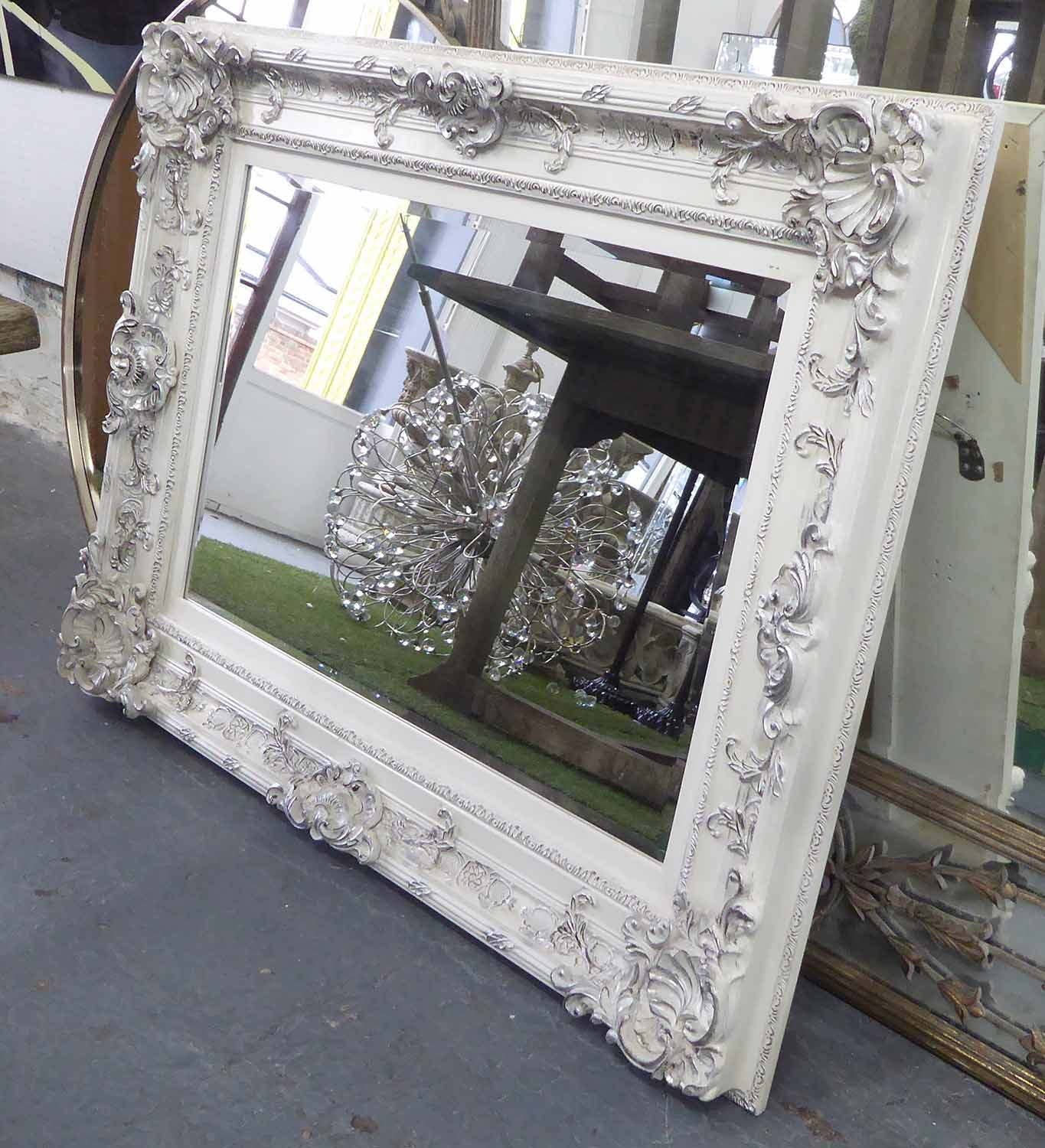 Lot 46 - WALL MIRROR, cream painted with silvered detail, and bevelled plate, 94cm x 125cm.