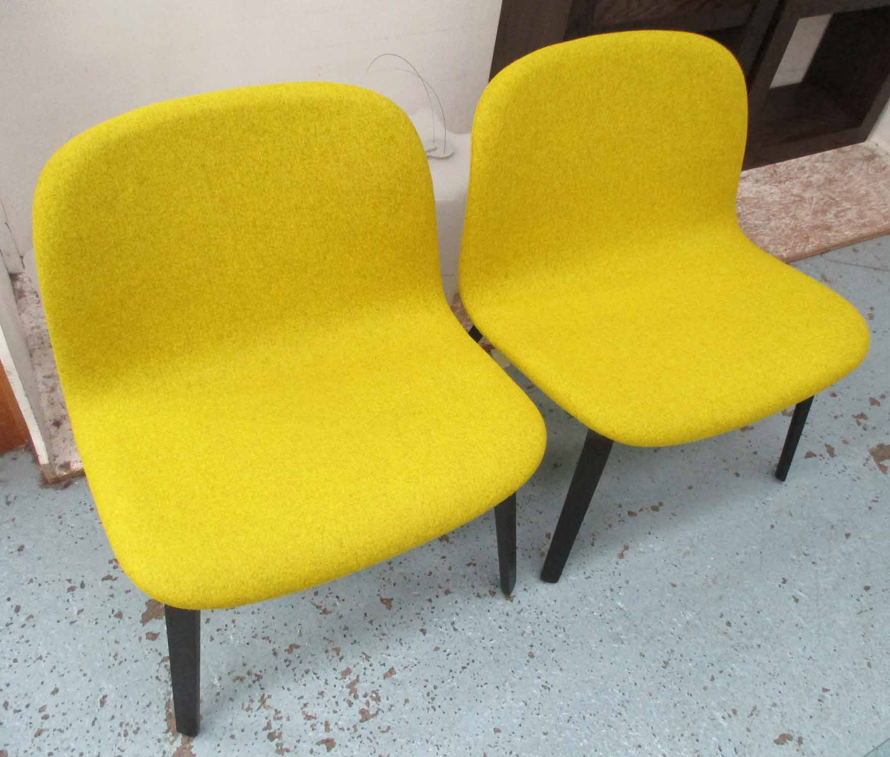 Lot 12 - MUUTO LOUNGE CHAIRS, a pair, in mustard upholstery on ebonised supports, designed by Mika Tolvanen,