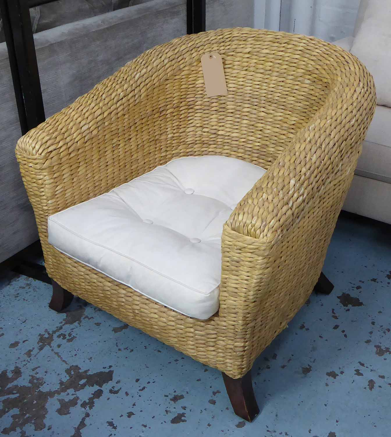 Lot 47 - CONSERVATORY WICKER SOFA, rounded back on splayed legs, with cushion and chair to match.