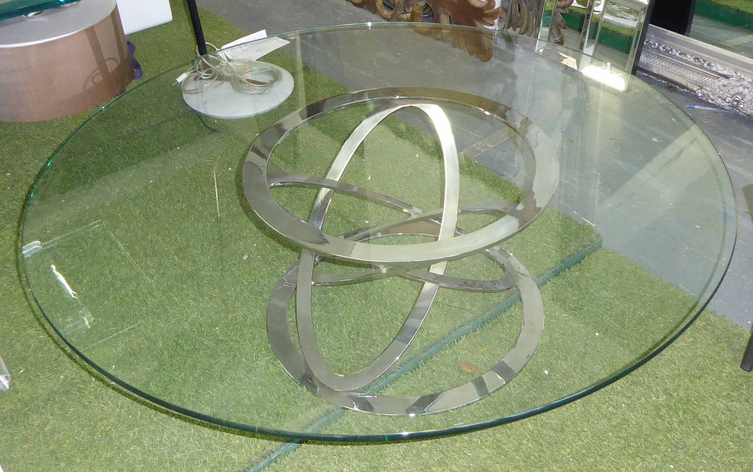 Lot 24 - OCCASIONAL TABLE, circular glass top on a chromed metal base, 129cm diam x 40cm H.