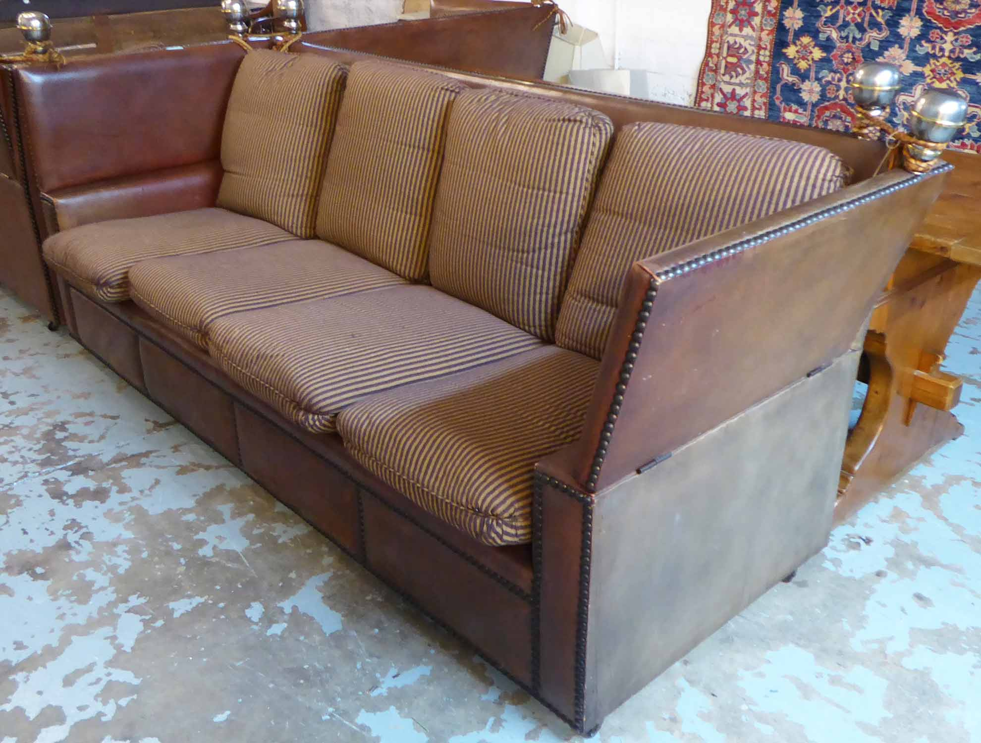 Lot 20 - KNOLE SOFA, of substantial proportions, brown leather with studded detail and striped cushions,