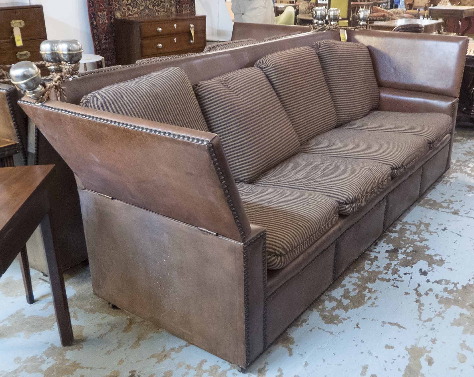 Lot 19 - KNOLE SOFA, of substantial proportions, brown leather with studded detail and striped cushions,