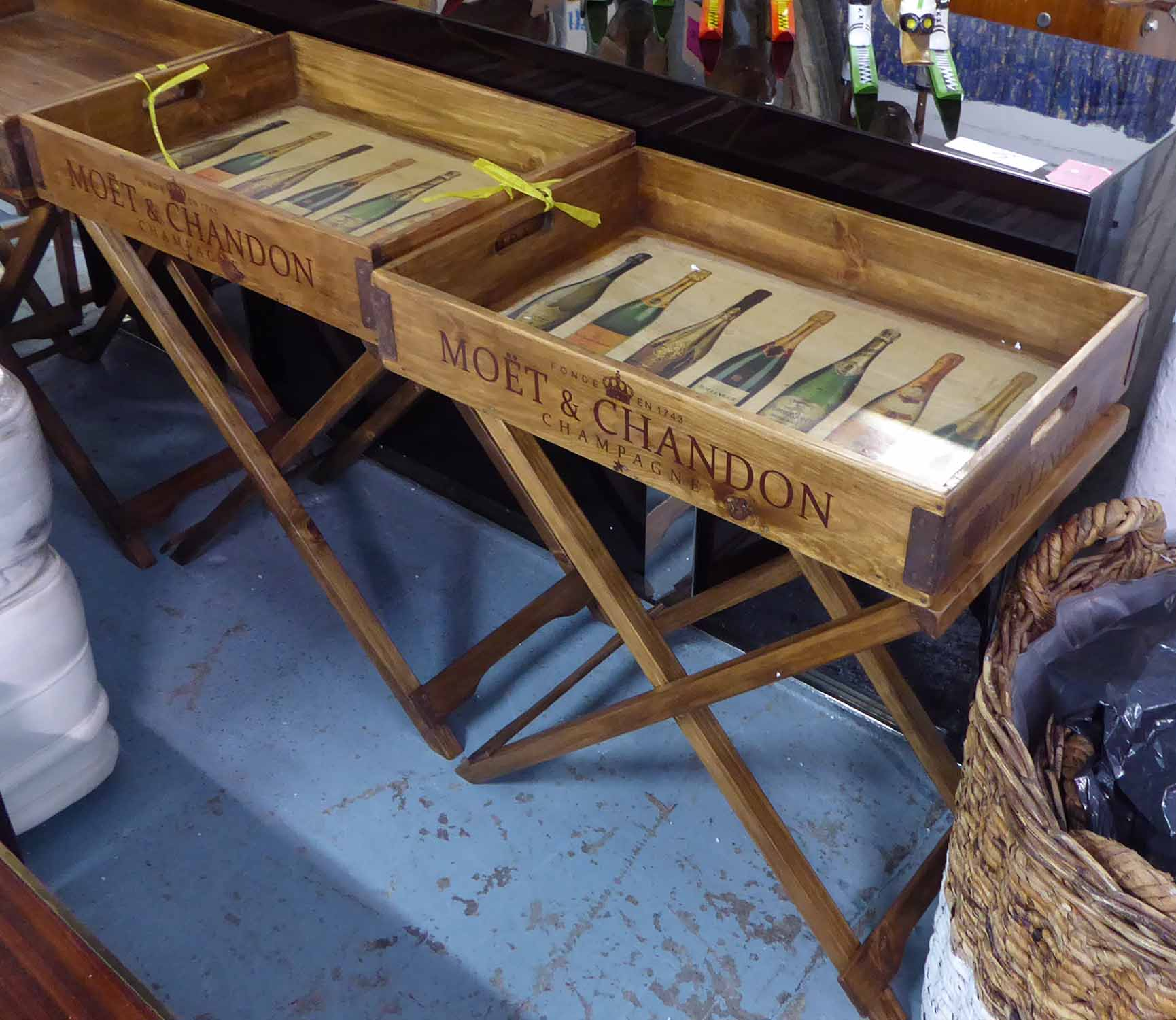 Lot 55 - DRINKS TRAYS, a pair, on stands, stamped with various champagne houses, 77cm H x 65cm W x 45cm D.