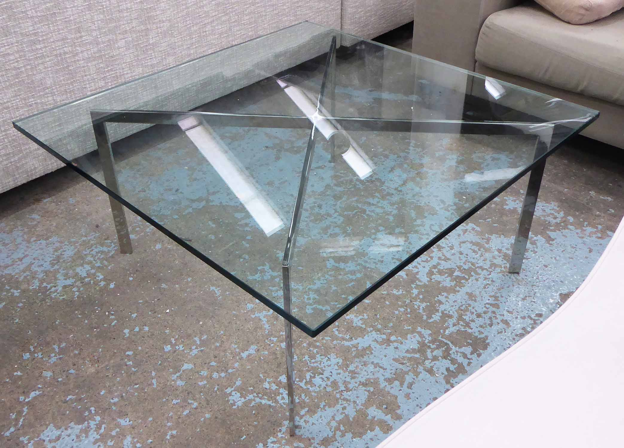 Lot 57 - LOW TABLE, Barcelona style, the glass top on a polished metal base, 100cm W x 100cm D x 47cm H.