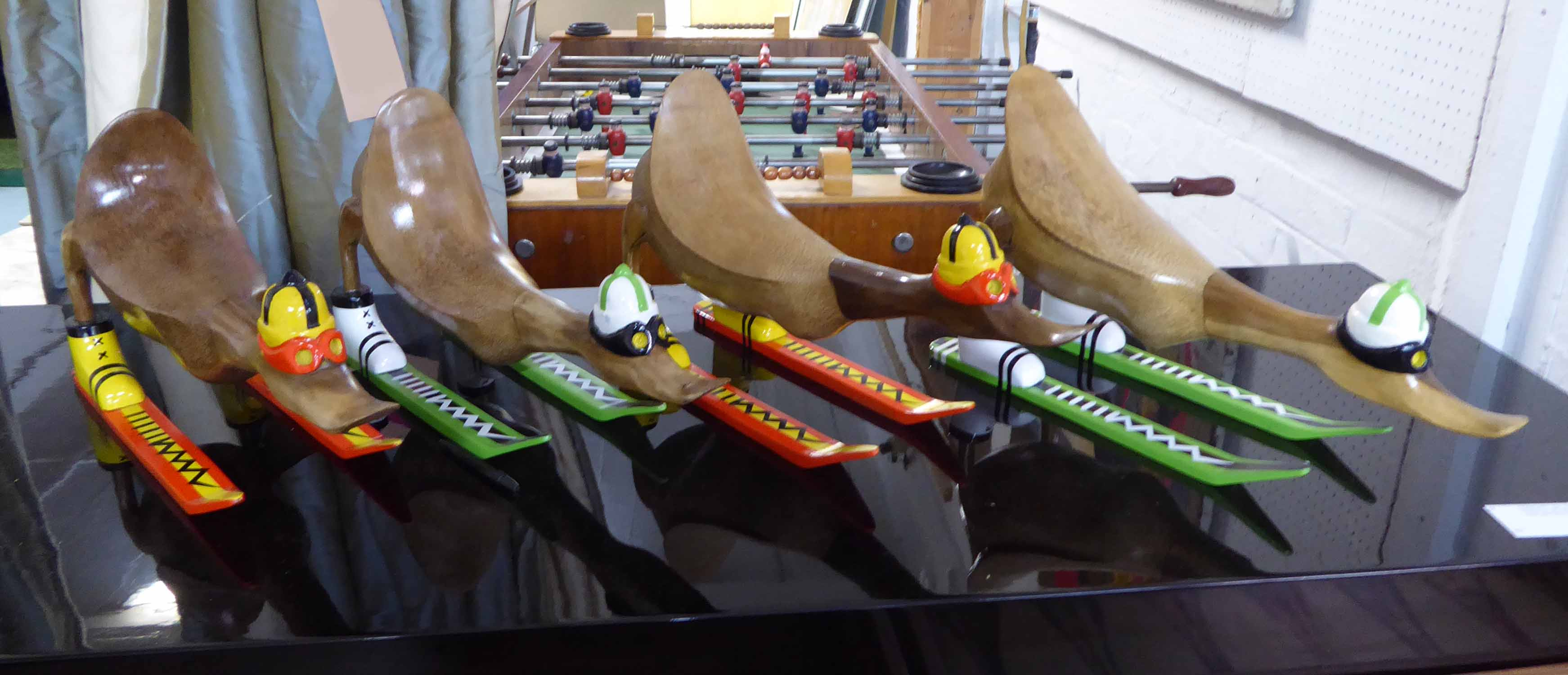 Lot 41 - THE SKIING DUCKS, a racing set of four, stylised form, 24cm H x 41cm W.