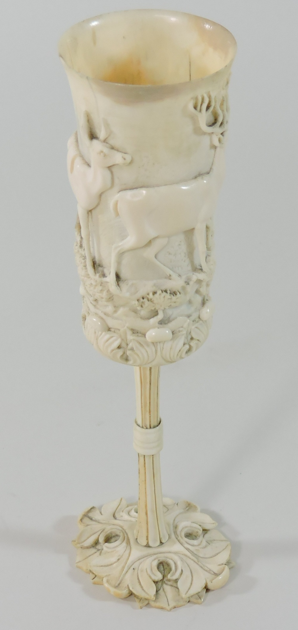 Lot 8 - A 19th century German carved and turned ivory hunting cup, of slender form,