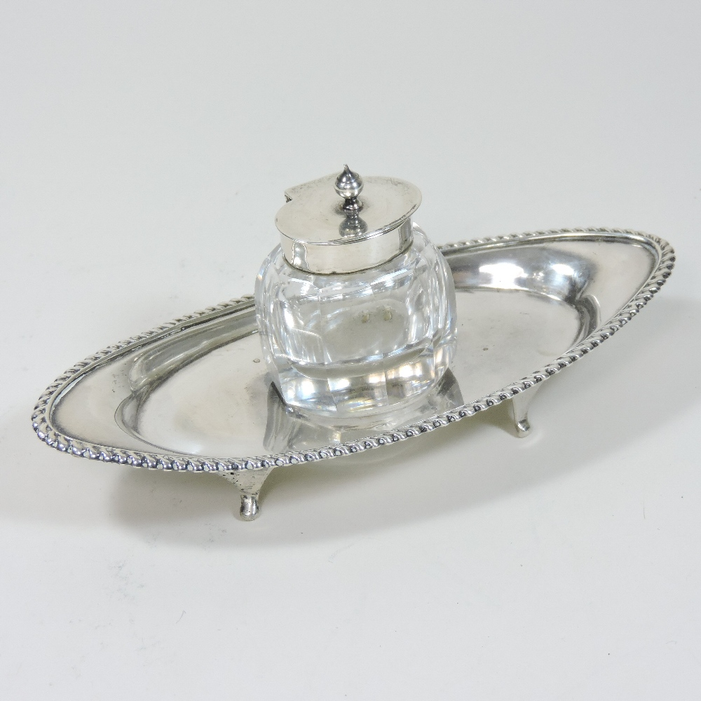 Lot 17 - An early 20th century silver desk stand, of elliptical shape, with a gadrooned border,