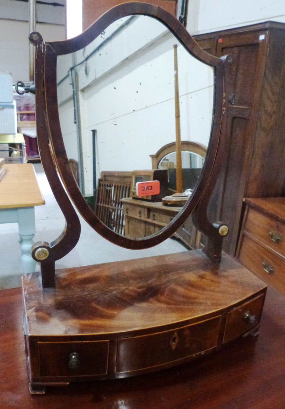 Lot 243 - A Regency mahogany dressing table glass, the shield plate on bowfronted base with three drawers,