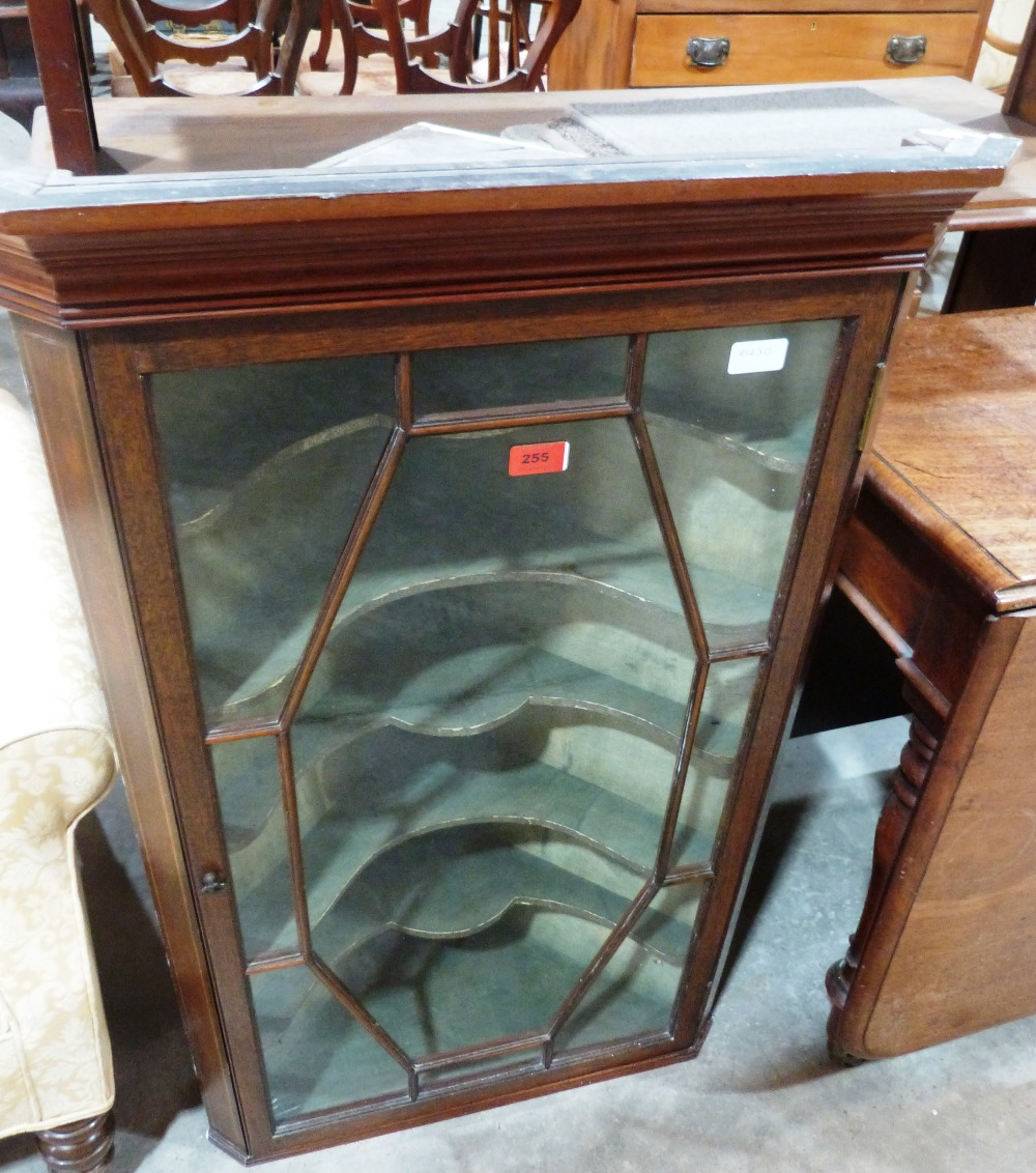 Lot 255 - A mahogany and line inlaid hanging corner cupboard enclosed by an astragal glazed door. 39' high