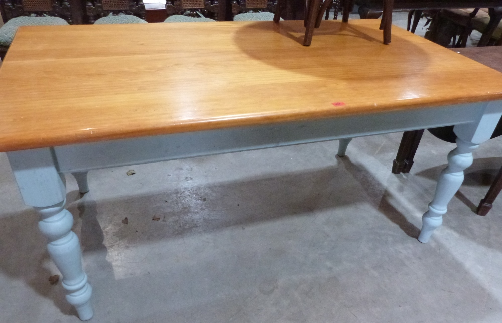 Lot 252 - A pine kitchen table on painted support with turned legs. 66' long