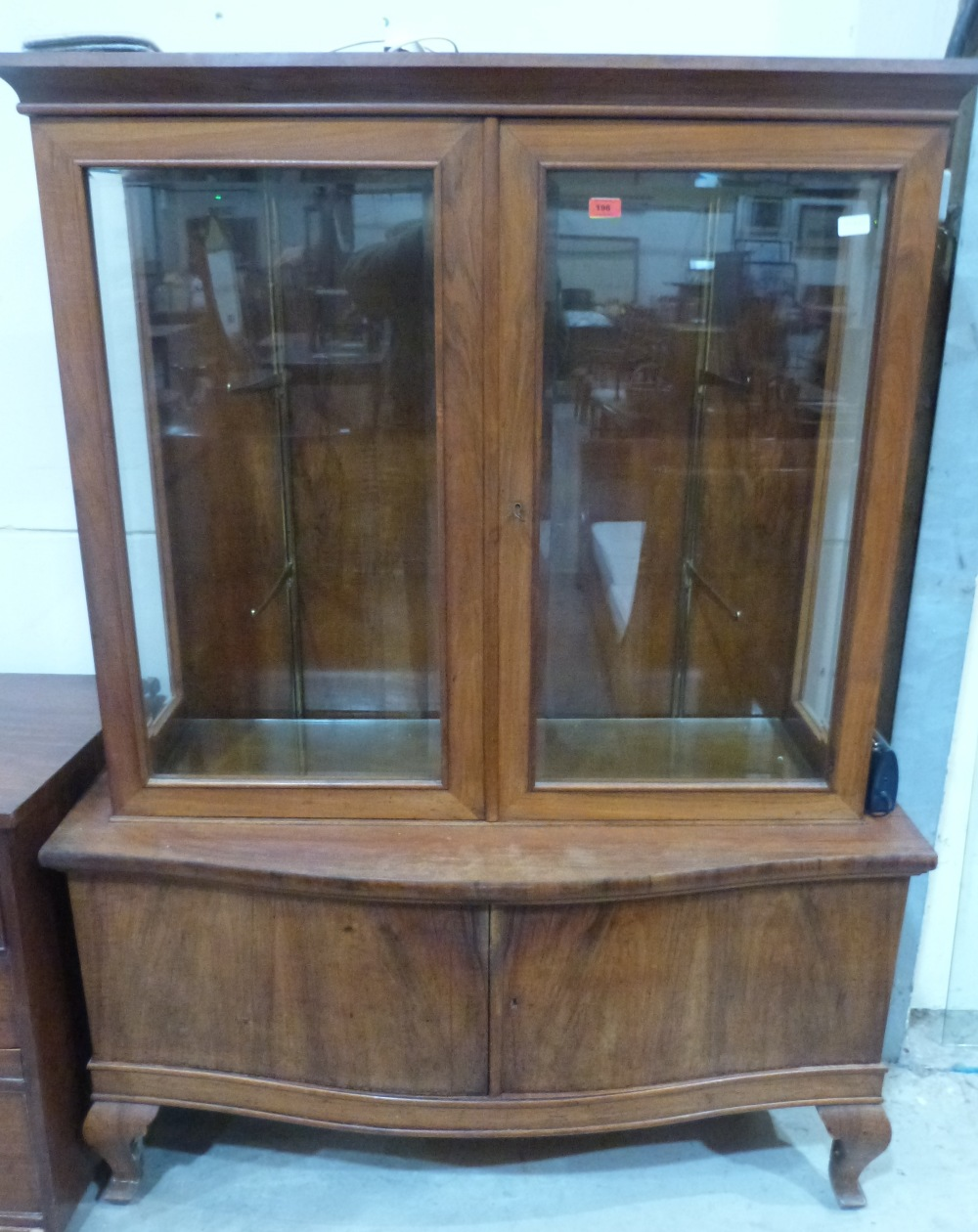 Lot 196 - A walnut display cabinet enclosed by a pair of glazed doors over serpentine cupboard base. 49' wide