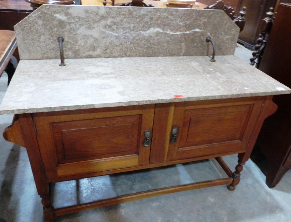 Lot 242 - An early 20th century oak washstand enclosed by a pair of doors under a marble top and splashback.