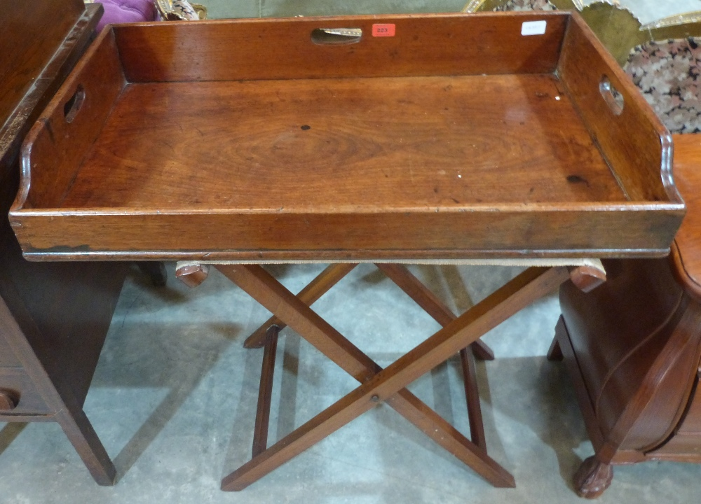 Lot 223 - A 19th century mahogany butler's serving tray on folding stand. 32' wide