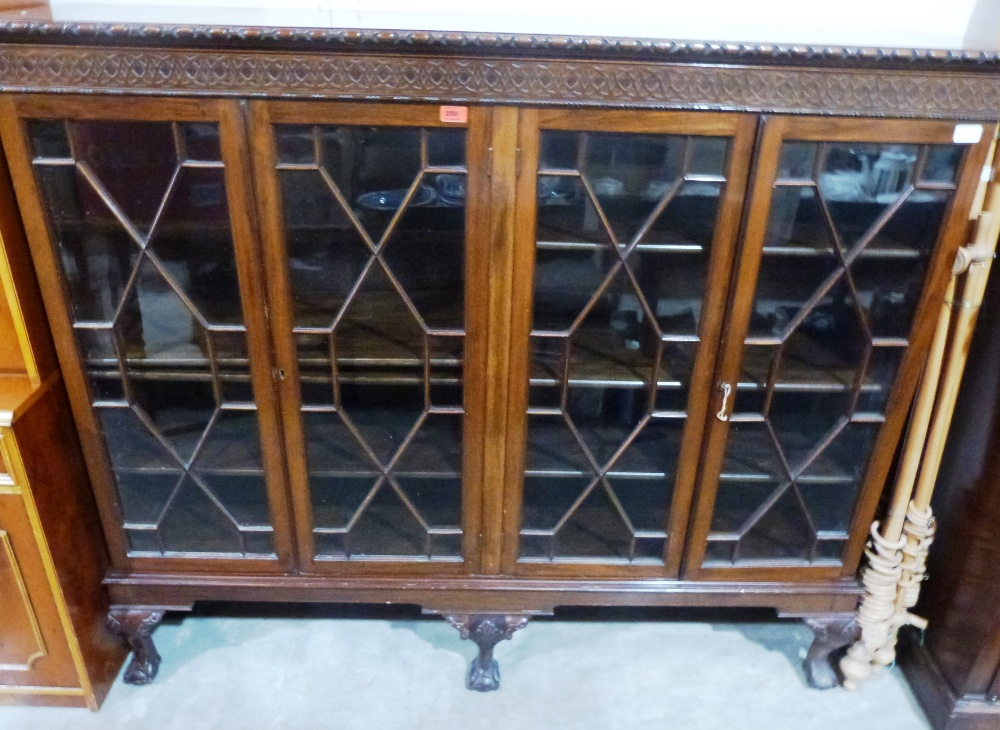 Lot 258 - An early 20th century mahogany bookcase enclosed by four astragal glazed doors on cabriole ball