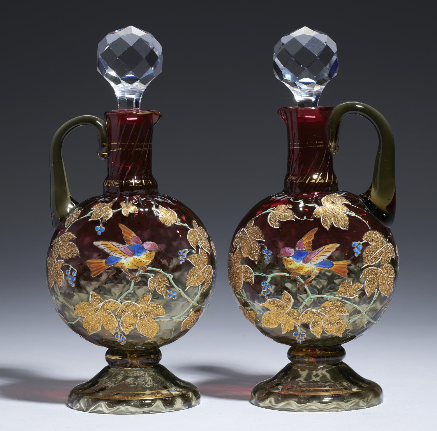 Lot 376 - A PAIR OF MOSER ENAMELLED AND GILT WRYTHEN FLUTED AND SHADED CRANBERRY GLASS DECANTERS, EARLY 20TH C